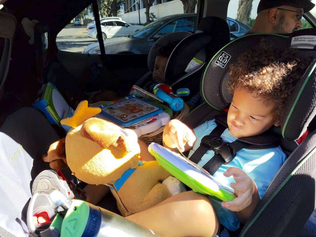 Toddlers in the car with toys for a roadtrip