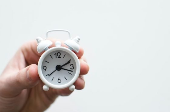person holding mini white alarm clock - Time management tips and hacks