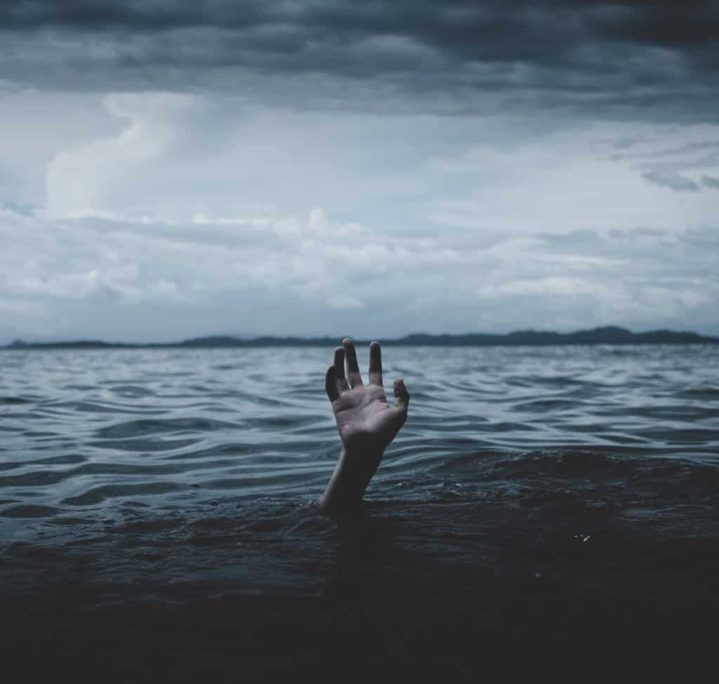 drowning person with hand reaching out from water