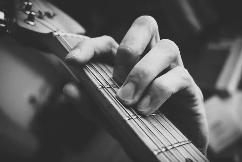 close up black and white shot of hand on guitar strings