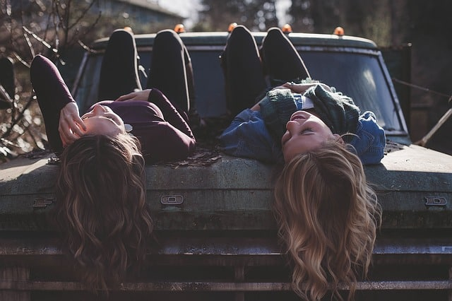 Two woman laying on top of an old ford truck