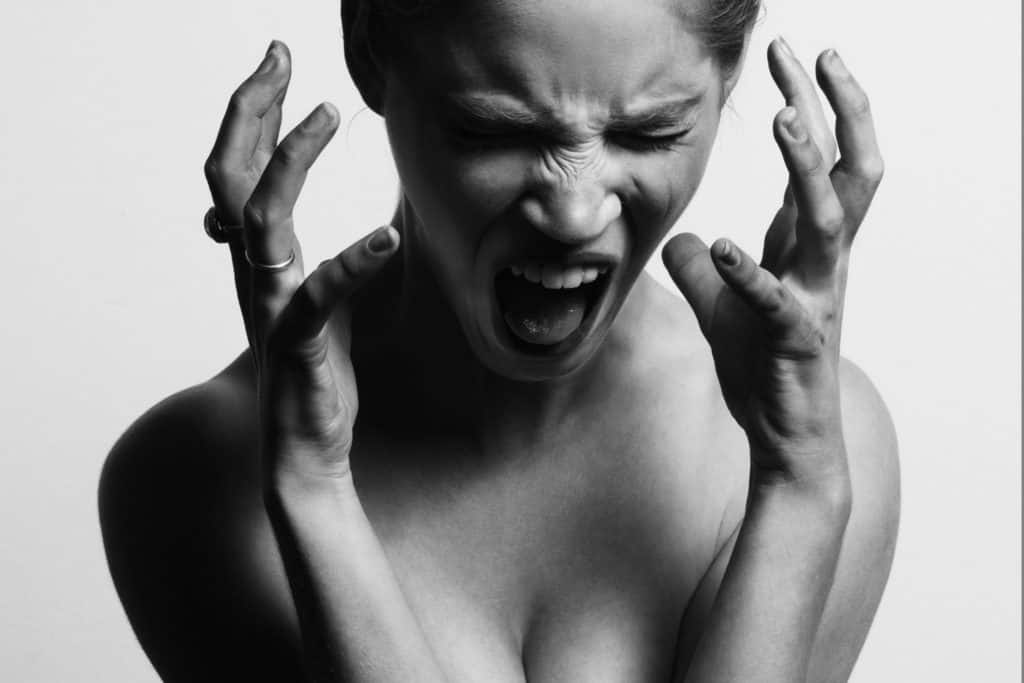 black and white close up of woman screaming with hands near face