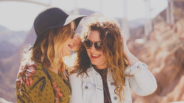 two women outside smiling together