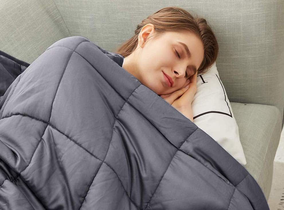 woman laying on her side with a weighted blanket over her
