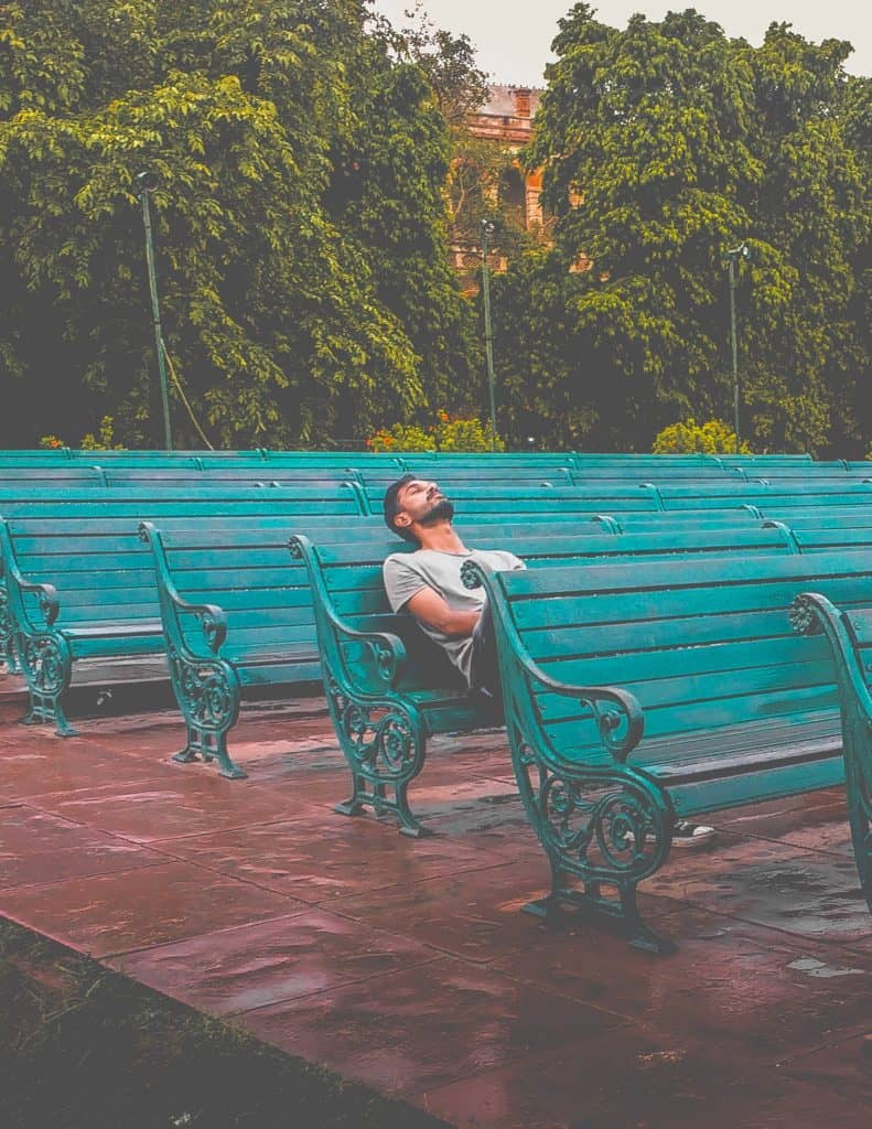 man sitting alone on a blue bench