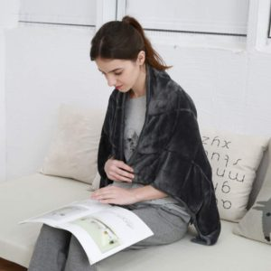 Woman reading a book with small weighted blanket over shoulders