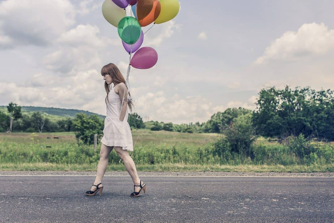 woman walking down the street with balloons