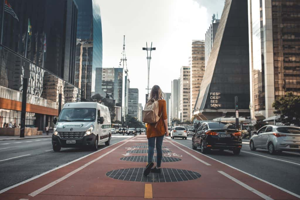 woman walking in the center median of traffic in a city
