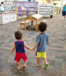 two toddlers holding hands in the library - How to save money with kids