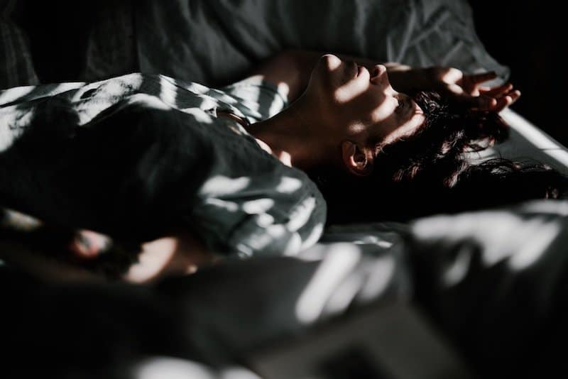 woman laying in bed in the dark - anxiety related insomnia